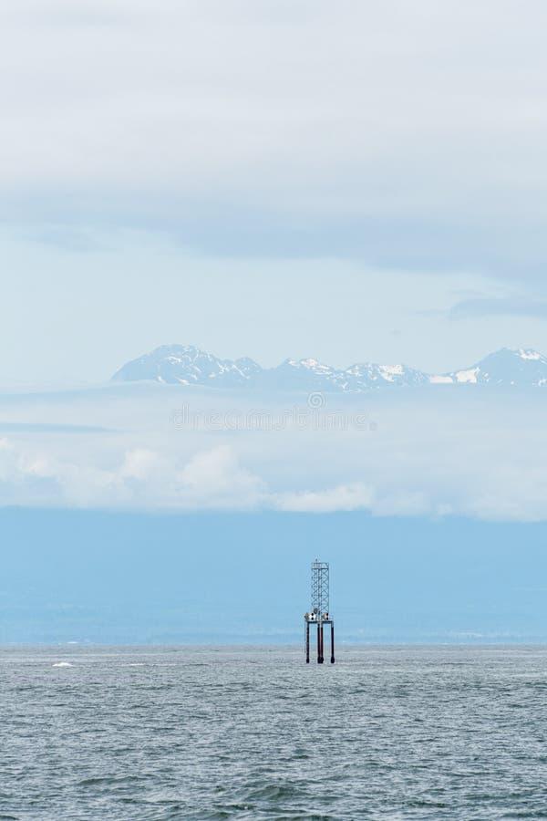 Scena blu nel mare di Salish con un indicatore di navigazione su un accatastamento, sulle montagne olimpiche blu nebbiose, su un  fotografia stock libera da diritti