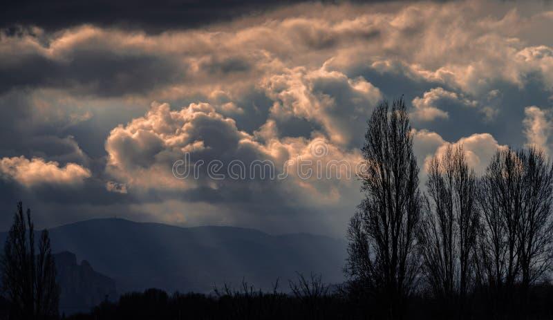 Scena con il cielo, i raggi di sole, le montagne e gli alberi tempestosi fotografie stock
