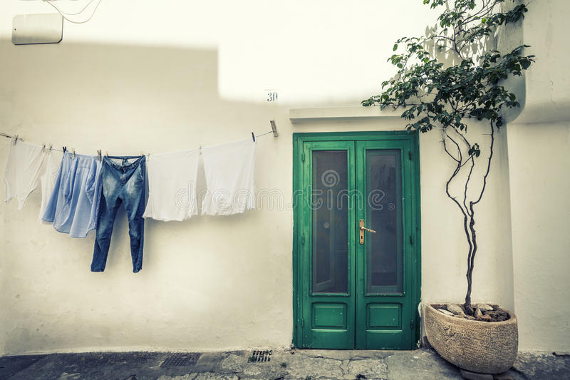 Scena d'annata italiana Vestiti che appendono per asciugarsi e vecchia casa immagine stock