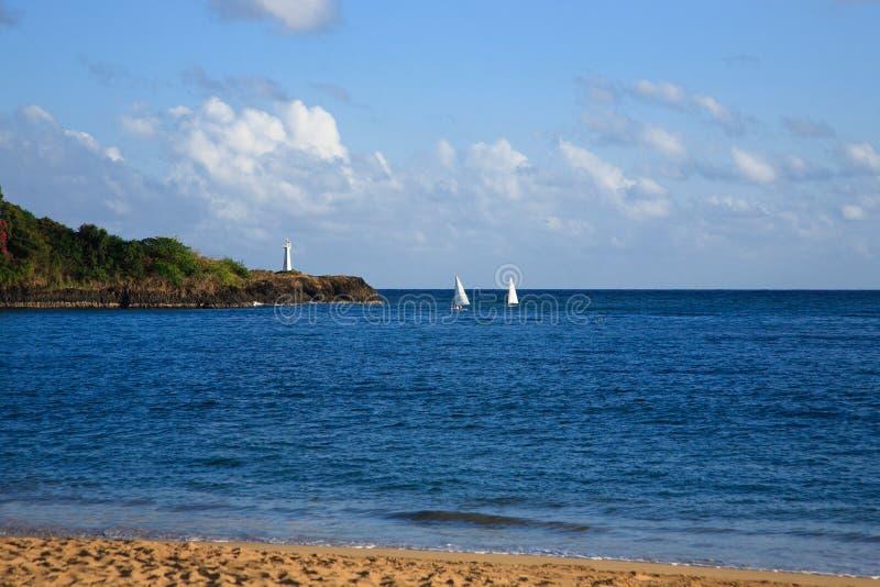 Scena dell'oceano con le barche a vela ed il faro fotografie stock libere da diritti