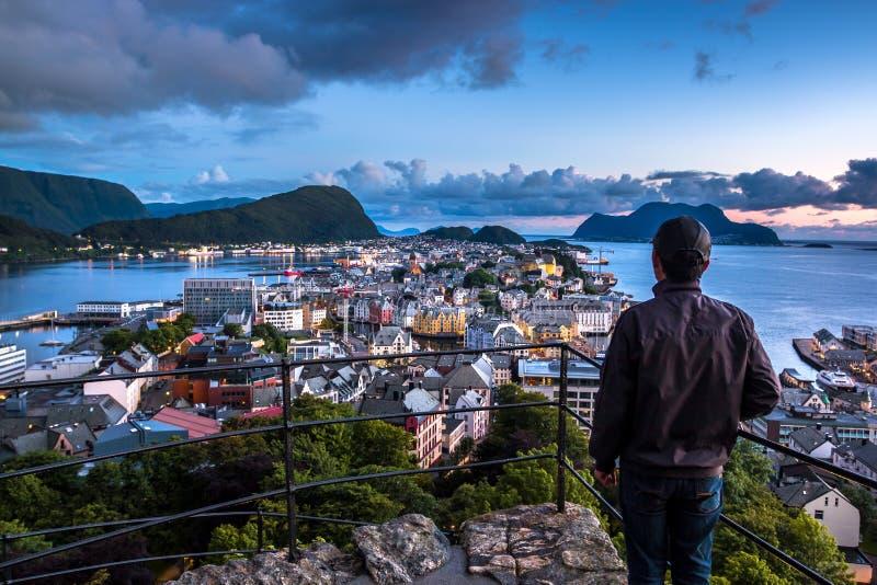 Scena della città con un uomo solo che osserva verso il centro di Alesund la notte immagini stock libere da diritti