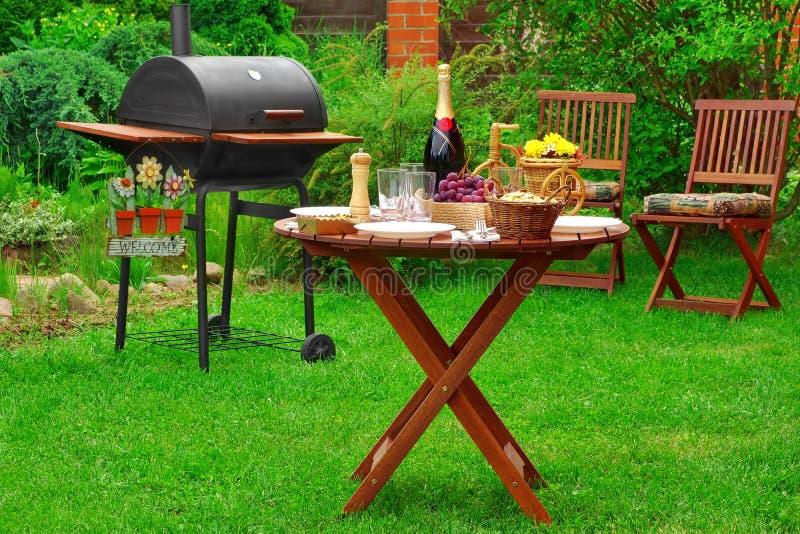 Scena della festa di famiglia del barbecue di estate con la griglia sul cortile il Gard immagine stock