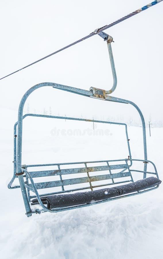 Scena della fine sull'ascensore di sci con i sedili che superano la montagna della neve immagine stock libera da diritti