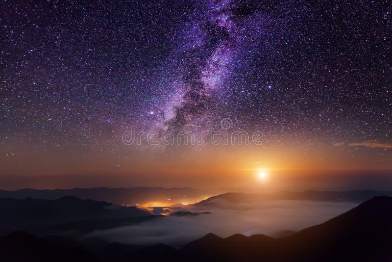 Scena della montagna con il cielo crepuscolare, la luna e le stelle brillanti della Via Lattea fotografia stock libera da diritti