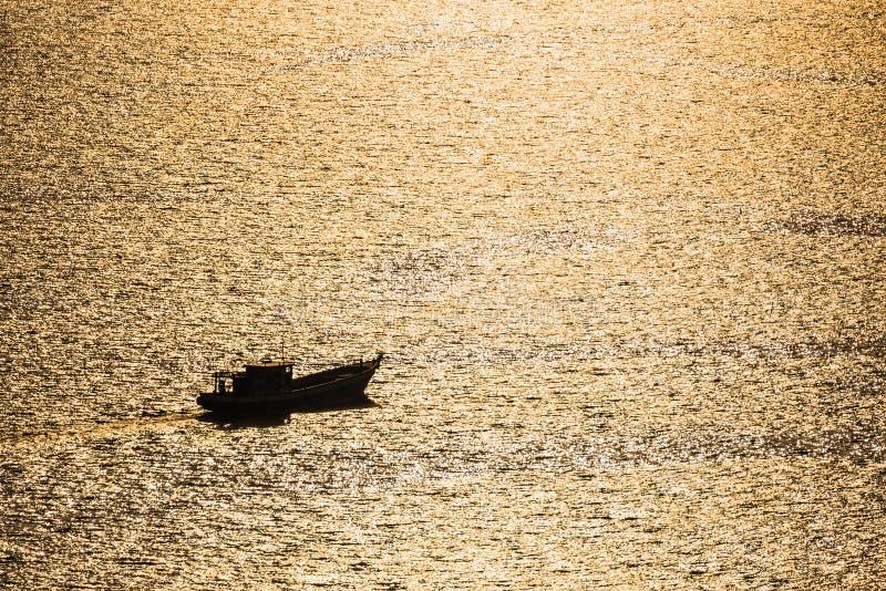 Scena della siluetta dell'imbarcazione a motore sul mare tropicale di andamane al tramonto a phuket, Tailandia fotografia stock