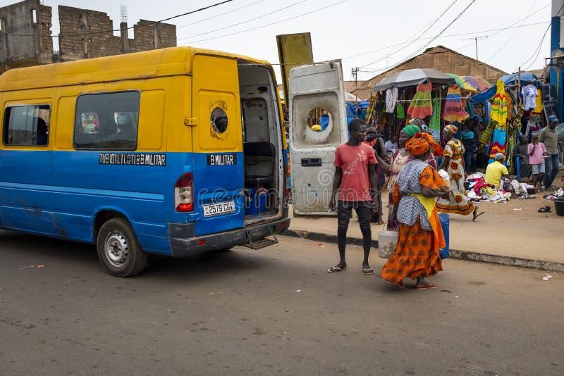 Scena della via nella città della Bissau con la gente che esce un bus pubblico Toca Toca al mercato di Bandim, in Guinea-Bissau fotografie stock