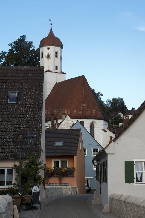 Scena della via in villaggio con la torre di orologio della chiesa nel fondo alla luce di pomeriggio fotografia stock