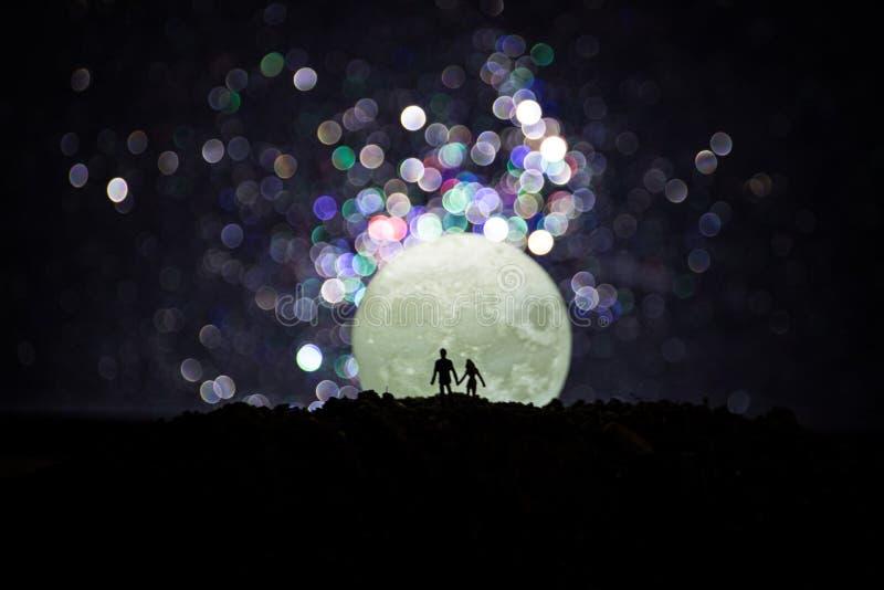 Scena di amore stupefacente Siluette di giovani coppie romantiche che stanno nell'ambito della luce di luna royalty illustrazione gratis