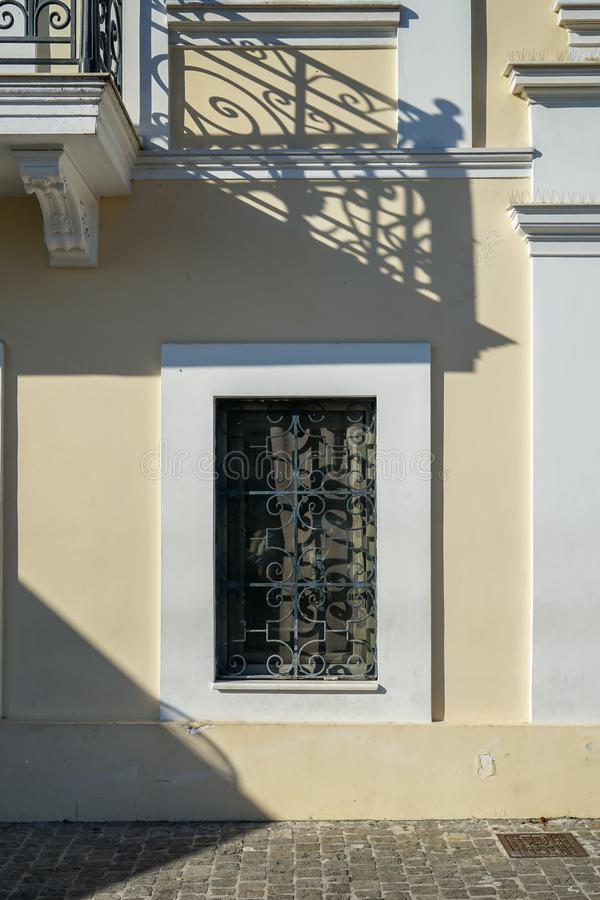 Scena di bei finestra e balcone urbani della facciata della costruzione con l'ombra della balaustra del ferro della colata in pit fotografia stock