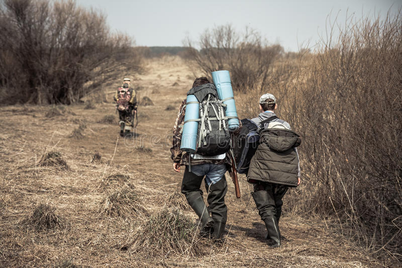 Scena di caccia con i cacciatori con gli zainhi e le munizioni di caccia che attraversano zona rurale con i cespugli durante la s fotografia stock libera da diritti