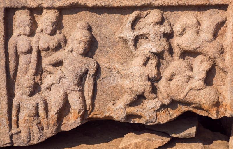 Scena di caccia, scultura scolpita sulla parete storica del tempio di pietra indiano in Pattadakal, India immagine stock