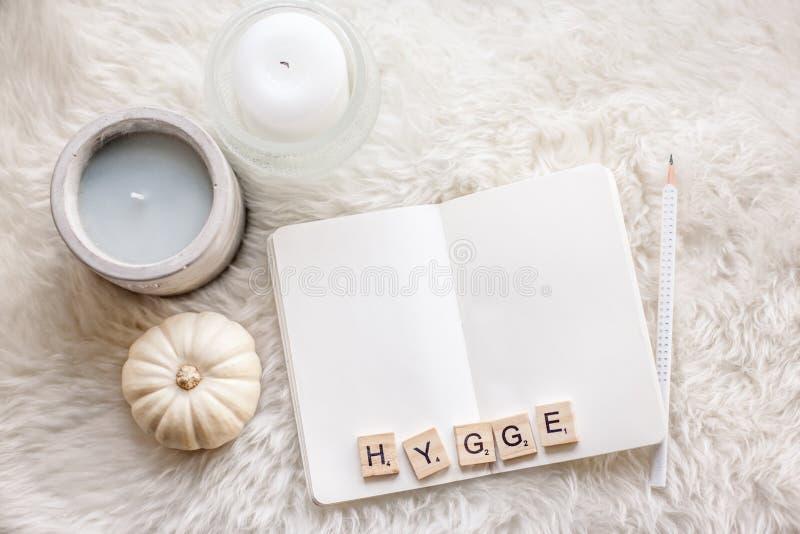 Scena di Hygge con lo sketchbook e le candele fotografia stock