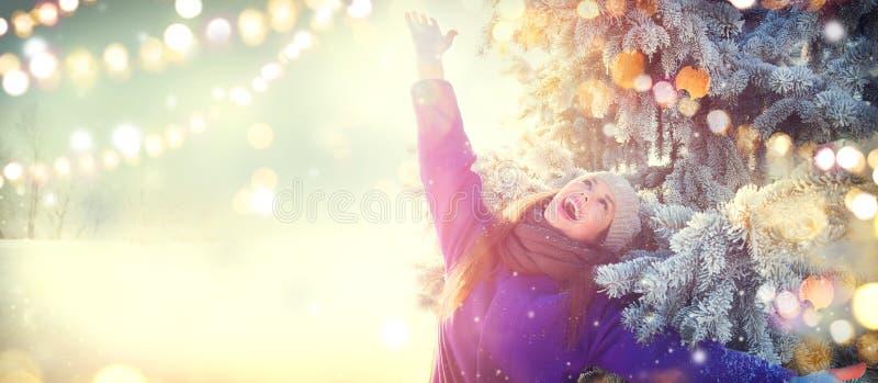 Scena di natale Ragazza allegra di bellezza di inverno divertendosi all'aperto nel parco di inverno sotto l'albero di Natale deco fotografia stock libera da diritti