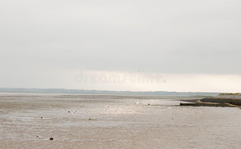 Scena di tramonto in cielo distante sopra lo scape della terra del mare della riva con le maree fotografia stock libera da diritti