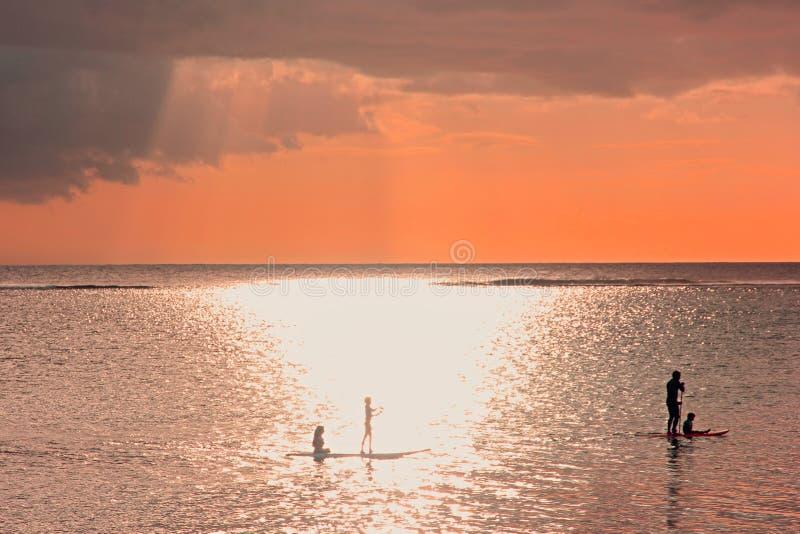 Scena di tramonto sul fondo venente di temporale Siluette della famiglia al tramonto sull'oceano Un padre con tre bambini sta rem immagini stock