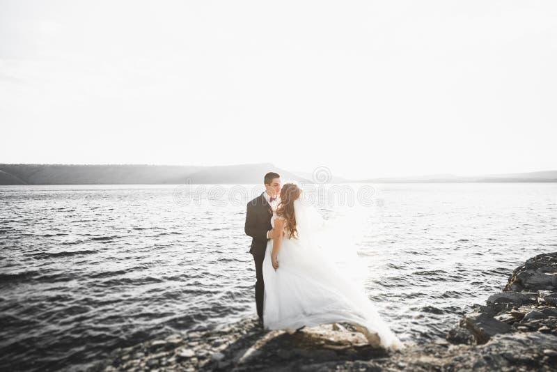 Scena felice e romantica appena di giovani coppie sposate di nozze che posano sulla bella spiaggia fotografia stock libera da diritti