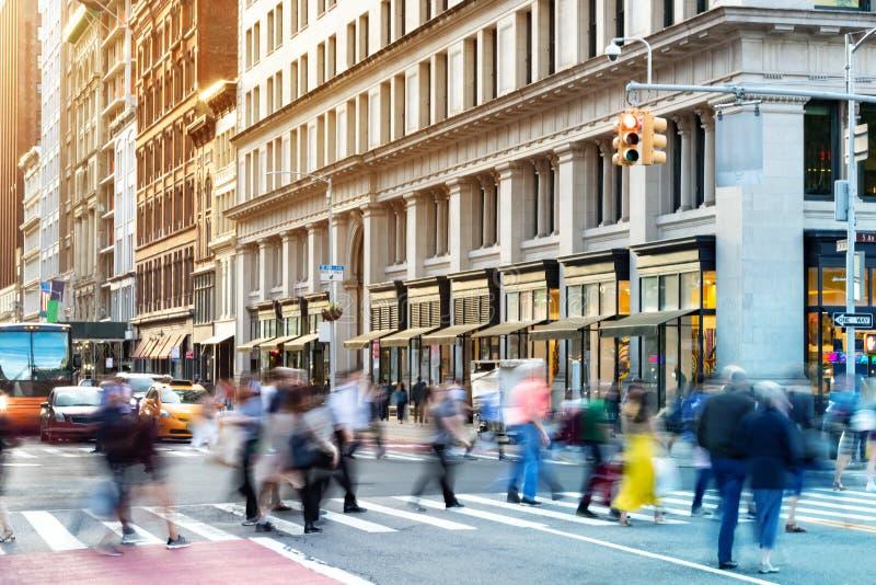 Scena na ulicy w Nowym Jorku z tłumami różnych ludzi w ruchu przez ruchliwe skrzyżowanie na 5. Alei w Midtown na Manhattanie obraz stock