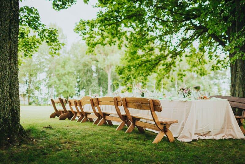 Scena parkowa na dworze z drewnianym stołem dekorowanym na uroczystość rodzinną zdjęcie stock