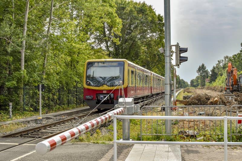 Scena przy Berlińskim linii kolejowej skrzyżowaniem z zamkniętą barierą która przechodzi pociągiem firma Deutsche Bahn, obrazy stock