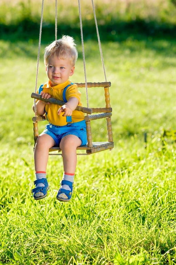 Scena rurale con il ragazzo del bambino che oscilla all'aperto immagini stock libere da diritti