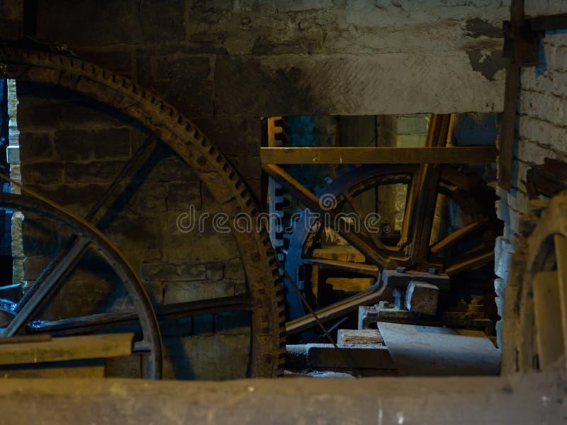 Scena rustica con le ruote dentate e gli ingranaggi giganti fotografia stock libera da diritti