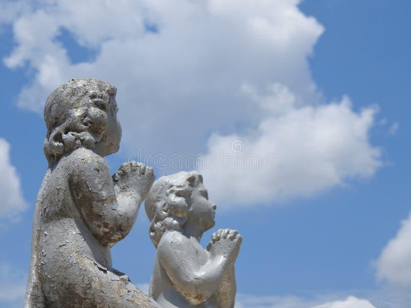 Scena in un cimitero: le due statue di pietra dei bambini con le loro mani insieme, pregando immagine stock
