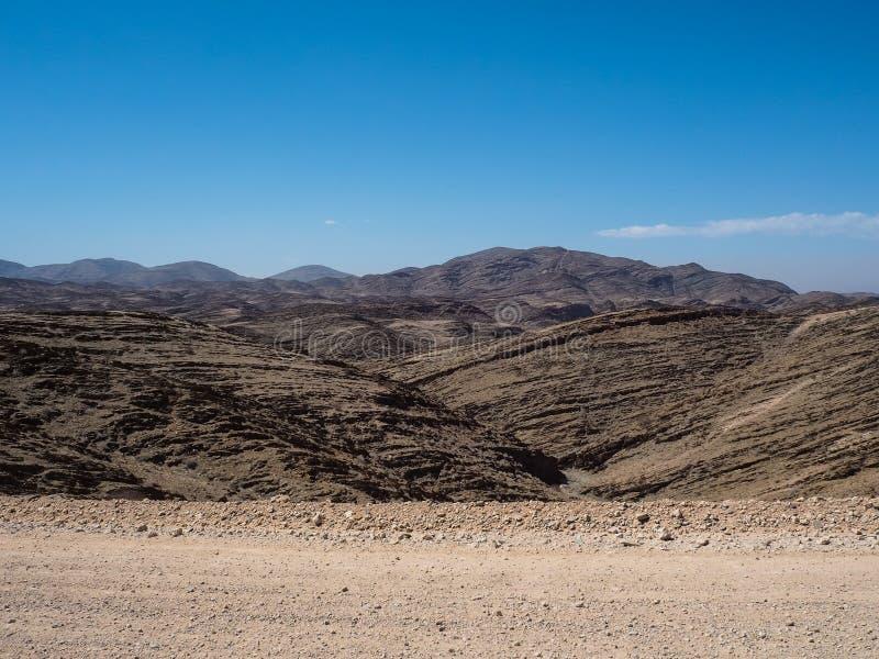 Scena wielki rockowy halny tekstur warstew panoramy krajobrazu widoku tło i jasny niebieskie niebo na niebrukowanej drodze grunto zdjęcie stock