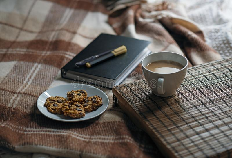 Scena z kawą na stole, ciastkach i notatniku, obraz stock