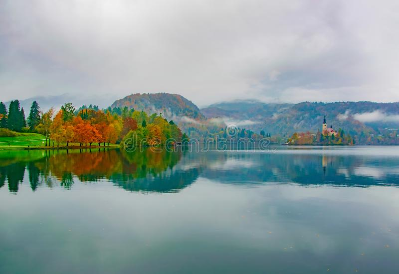 Scenari d'autunno di alberi colorati riflessi nelle acque del lago, Lago Bled, Slovenia fotografie stock libere da diritti