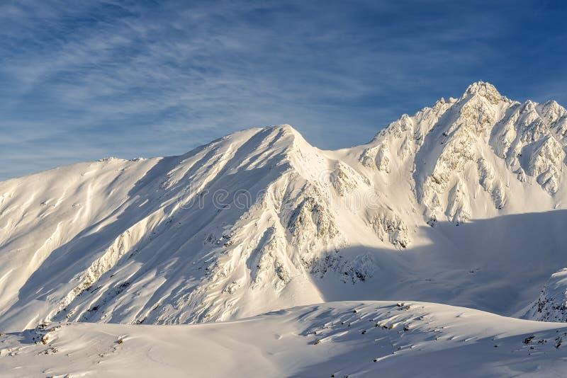 Scenari di montagna alpina austriaca ricoperta di strato di neve in inverno al caldo tramonto o all'alba Schiena azzurra su fotografia stock
