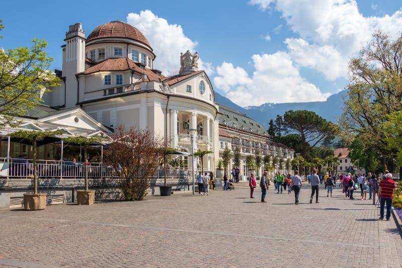 Scenario della via della passeggiata del passante con la facciata di costruzione famosa, Kurhaus in Meran Provincia Bolzano, Tiro immagini stock