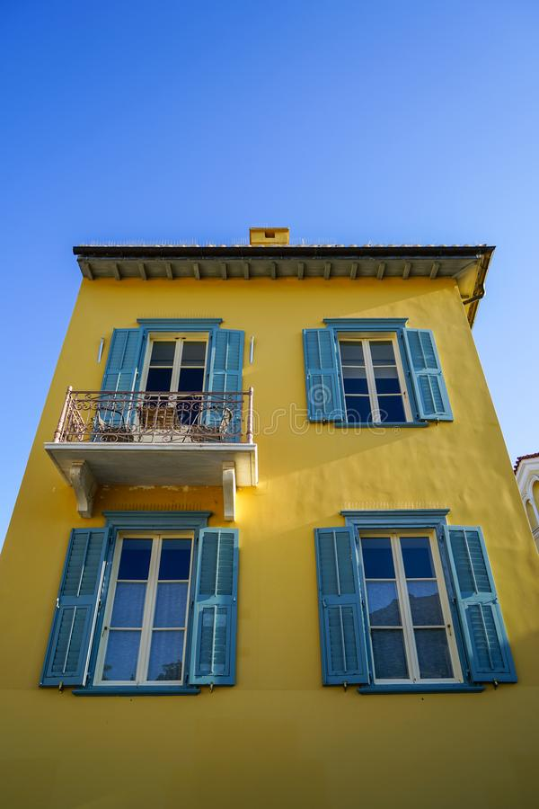 Scene of beautiful urban building facade background in pastel bright yellow plaster paint wall, light blue door and window shutter. With sky background, Athens stock photography