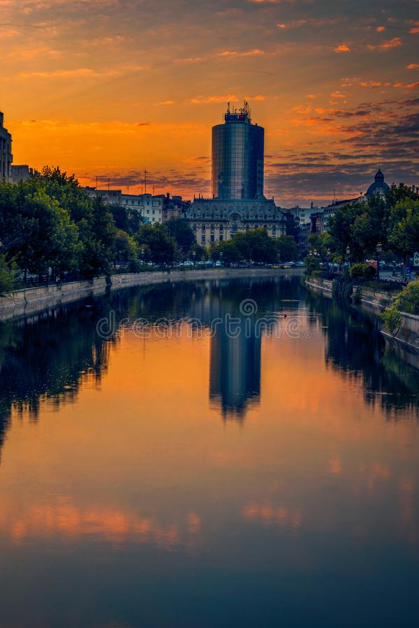 Scene from the Bucharest city in Romania early in the morning wi. Th a big glass building skyscraper in the background and a river with some ducks swimming stock photo