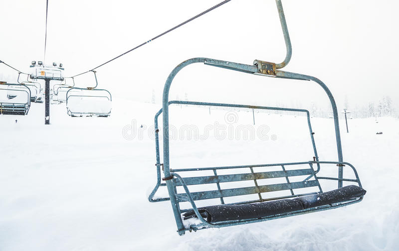 Scene Of Close Up Ski Lift With Seats Going Over The Snow Mounta ...