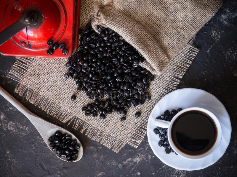 scene about coffee in top view. Vintage red coffee grinder, cup, wooden spoon and bag of coffee beans royalty free stock photos