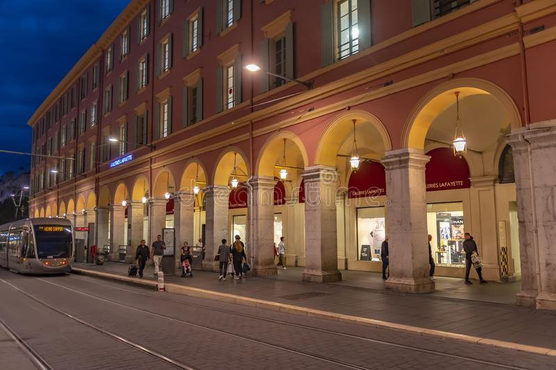 Scene on a evening in Nice in front of the department store Galeries Lafayette with strolling people and a tram stock image