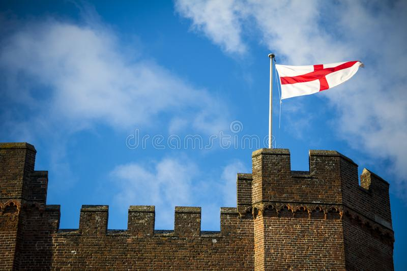 England flag flying above castle fortifications with blue sky royalty free stock image