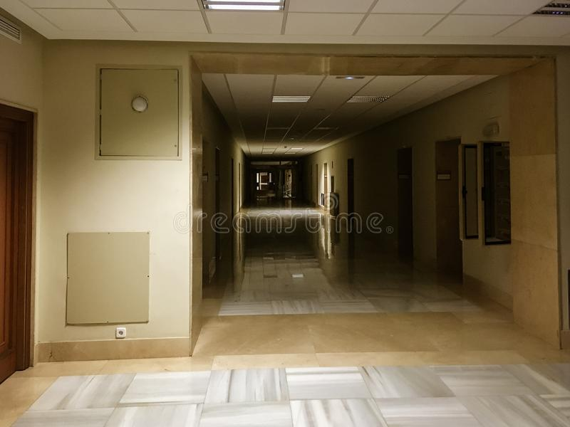 A long, dark corridor with no one, at night. A scene of fear where in the long corridor the shadows play with the lights creating a landscape that gives chills royalty free stock image
