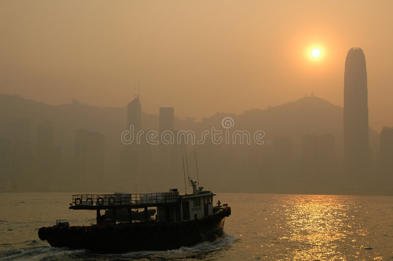 Scene - Hong Kong. Boat sailing towards Hong Kong island at sunset royalty free stock images
