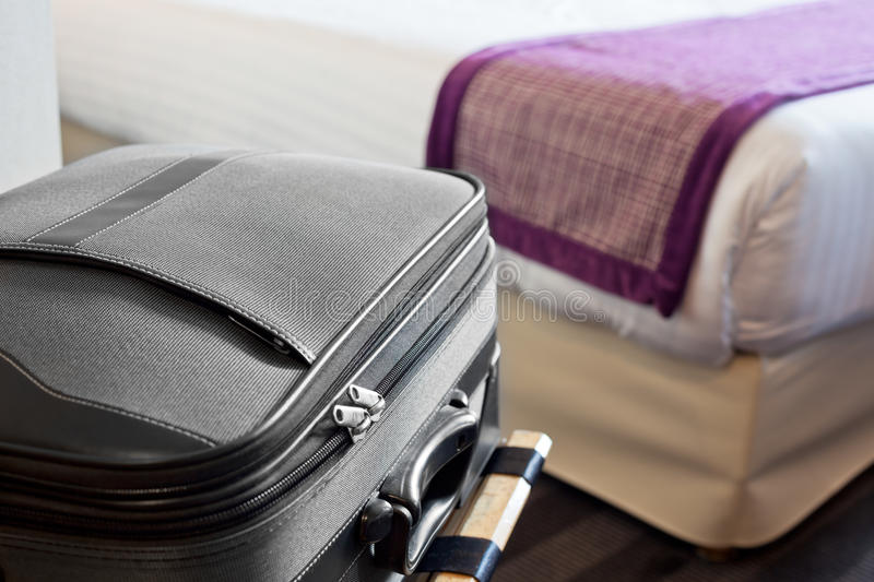 Scene in hotel room. Hotel room with a suitcase on the luggage place and the bed royalty free stock image