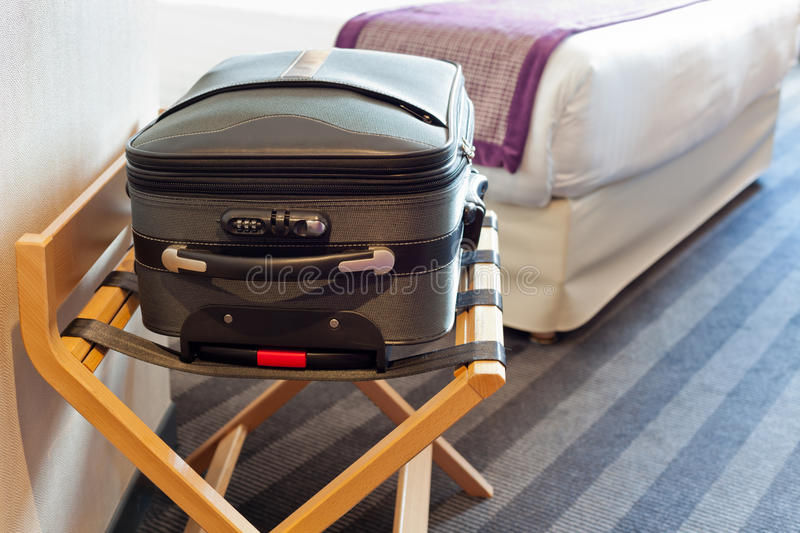 Scene in hotel room. Hotel room with a suitcase on the luggage place and the bed royalty free stock photos
