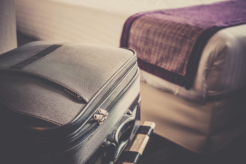 Scene in hotel room. Hotel room with a suitcase on the luggage place and the bed. Filtered shot royalty free stock photography