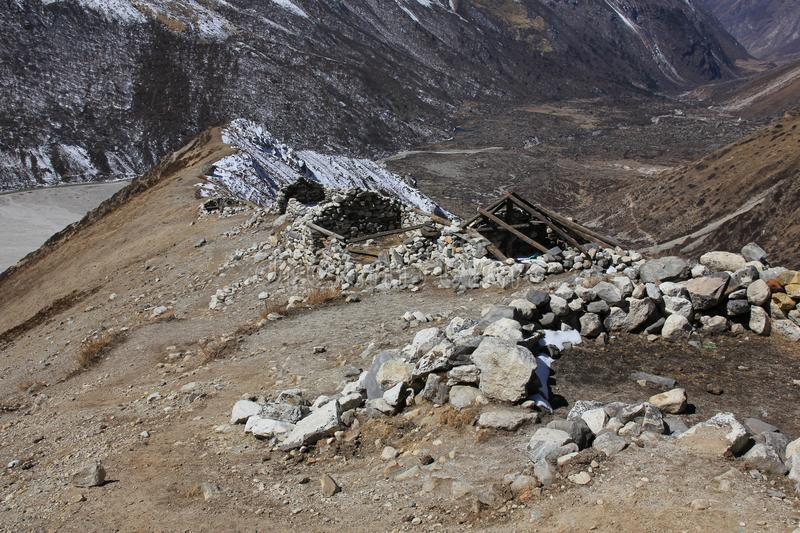 Roofless yak herder huts on the way to Tserko Ri, Langtang valley, Nepal. Scene in the Langtang National Park, Nepal. Roofless stone huts on a mountain ridge stock photos