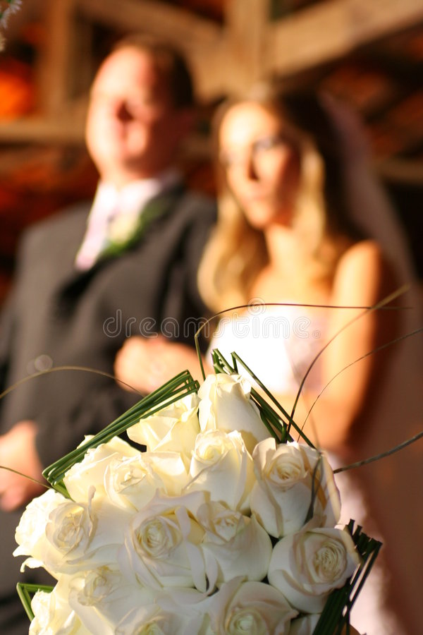Scene from a marriage. Scene of a religious marriage, focus on bouquet, with the grooms blurred background stock photography