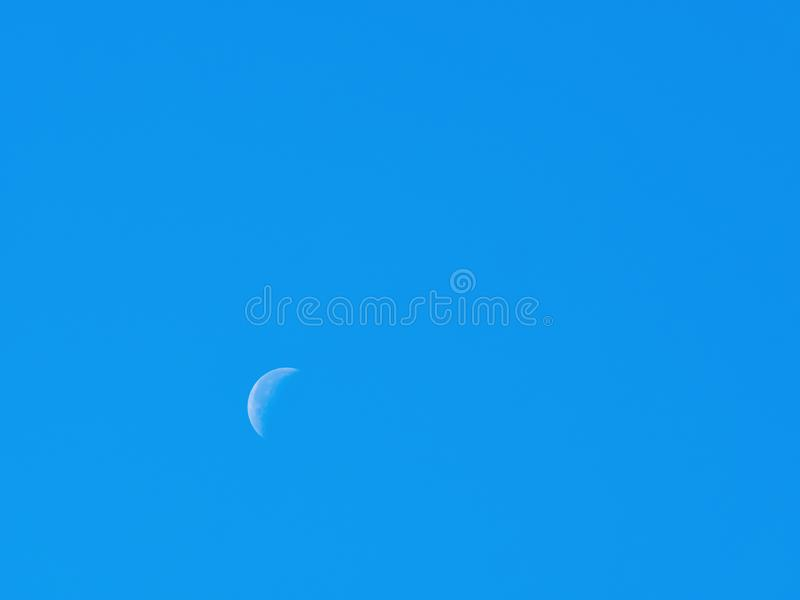 Moon during the day with blue sky stock photos