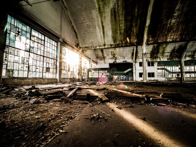 What light through yonder window breaks. A scene from an old abandoned factory with the sun breaking through the already broken windows. It`s messy, gravel floor stock photo