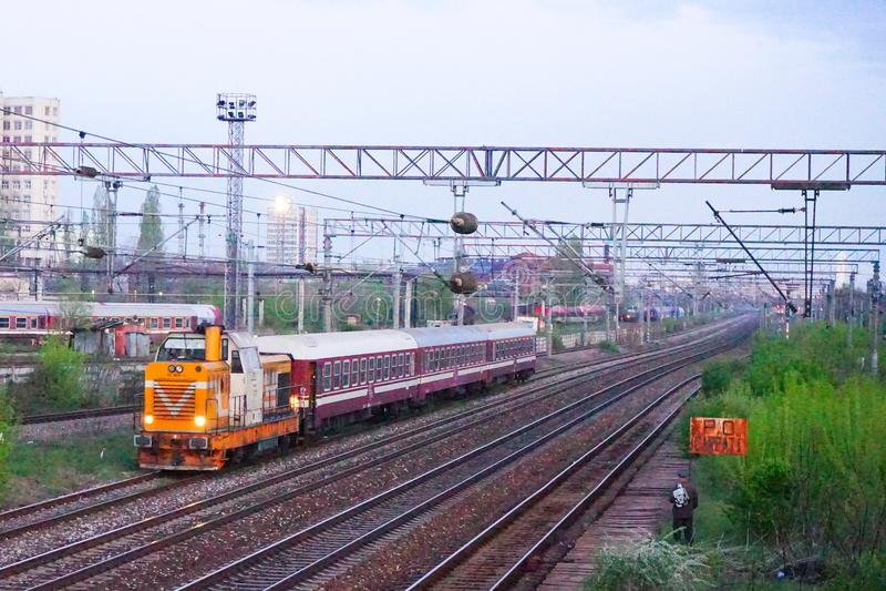 Scene of orange locomotive and red train in Carpati station, Bucharest, CFR. Train passing Carpati station in Bucharest Romania nightscene royalty free stock photo