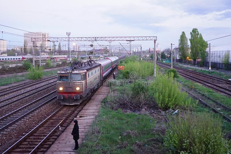 Scene of red locomotive and red train in Carpati station, Bucharest, CFR. Train passing Carpati station in Bucharest Romania. women on the platform waiting for stock photos