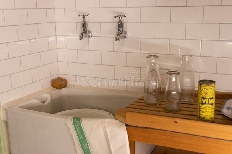 A scene from a 1960`s kitchen with tiles, a butler sink, wooden draining board and Vim cleaning powder stock photo