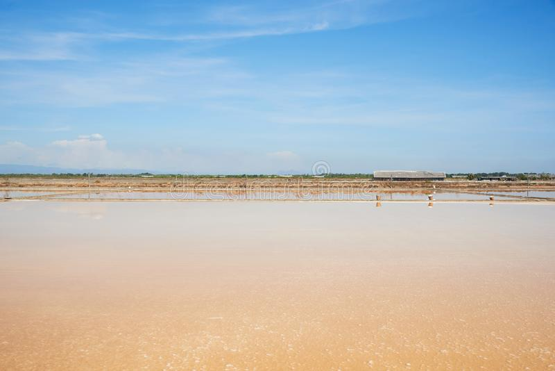 Scene of salt pan field on blue sky background. Rural scene of salt pan field on blue sky background in sunny day stock photography